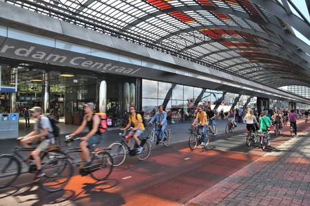 AMSTERDAM, NETHERLANDS - JULY 9, 2017: Cyclists visit Amsterdam Central Station (Centraal) in the Netherlands. The station was opened in 1889 and has 162.000 daily passengers.