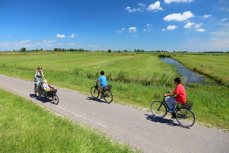 cycleway: ZAANDAM, NETHERLANDS - JULY 9, 2017: Cyclists visit polder countryside of Kalverpolder in Zaandam. Netherlands has 35,000 km of cycleways physically separated from motor traffic. Editorial