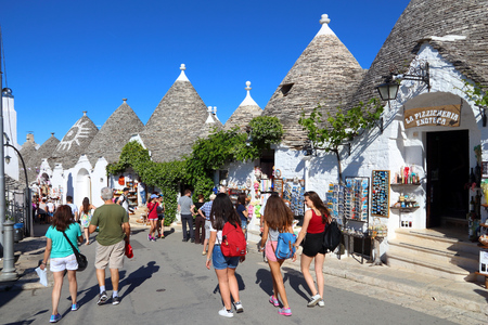 ALBEROBELLO, ITALY - MAY 29, 2017: People visit Alberobello, Italy. Alberobello and its trulli houses are a UNESCO World Heritage Site. Editorial