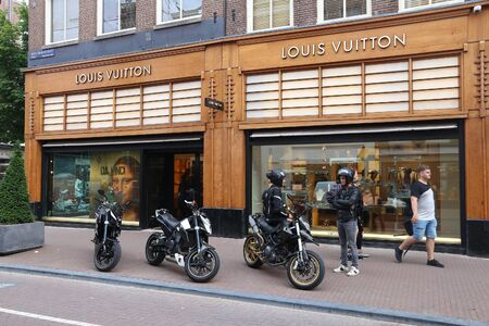 upscale: AMSTERDAM, NETHERLANDS - JULY 10, 2017: People visit Louis Vuitton shop at P.C. Hooftstraat in Amsterdam. Pieter Cornelis Hooftstraat is the ultimate upscale shopping street in the Netherlands.