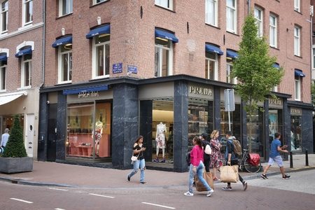 upscale: AMSTERDAM, NETHERLANDS - JULY 10, 2017: People visit Prada store at P.C. Hooftstraat in Amsterdam. Pieter Cornelis Hooftstraat is the ultimate upscale shopping street in the Netherlands. Editorial