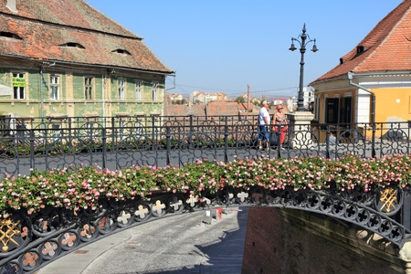 SIBIU, ROMANIA - AUGUST 24, 2012: People visit famous Bridge of Lies in Sibiu, Romania. Sibius tourism is growing with 284,513 museum visitors in 2001 and 879,486 visitors in 2009. Editorial
