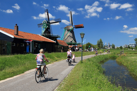ZAANSE SCHANS, NETHERLANDS - JULY 9, 2017: Cyclists visit windmills of Zaanse Schans. Netherlands has 35,000 km of cycleways physically separated from motor traffic.