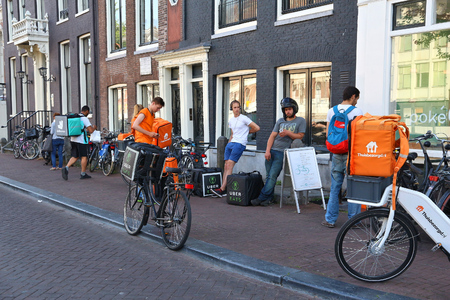 AMSTERDAM, NETHERLANDS - JULY 9, 2017: Uber Eats, Thuisbezorgd and Deliveroo food couriers wait in Amsterdam, Netherlands. Bicycle food delivery is popular in Amsterdam. 新闻类图片