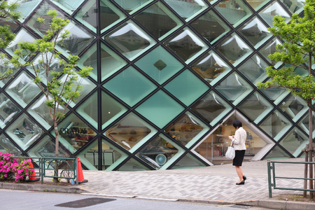 TOKYO, JAPAN - MAY 9, 2012: Person walks by Prada store in Omotesando, Tokyo. The Italian fashion company is present in 65 countries with 250 single brand shops. It was founded in 1913.