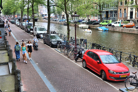 AMSTERDAM, NETHERLANDS - JULY 10, 2017: People visit Herengracht canal in Amsterdam, Netherlands. Amsterdam is the capital city of The Netherlands. Editorial