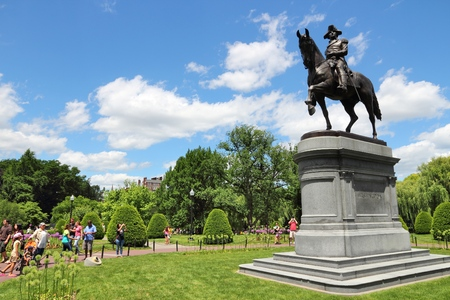 BOSTON, USA - JUNE 9, 2013: People visit Washington Monument at Public Garden in Boston. Public Garden dates back to 1837 and is a registered monument.