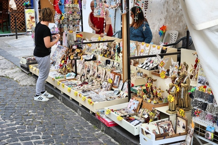 MONTE SANT ANGELO, ITALY - JUNE 6, 2017: People buy religious souvenirs in Monte Sant, Angelo, Italy. The sanctuary town is part of UNESCO World Heritage Site: Longobards Places of Power. Banco de Imagens - 85227558