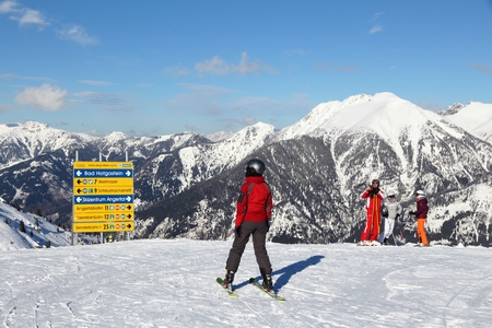 skiers: BAD HOFGASTEIN, AUSTRIA - MARCH 9, 2016: People analyze trail signs in Bad Hofgastein. It is part of Ski Amade, one of largest ski regions in Europe with 760km of ski runs.