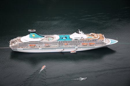 GEIRANGER, NORWAY - JULY 19, 2015: MV Artania cruise ship in Geiranger, Norway. The ship was made in Helsinki Shipyard by Wartsila. It is operated by Phoenix Reisen, German tour operator.