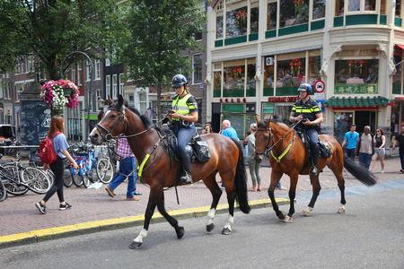 AMSTERDAM, NETHERLANDS - JULY 10, 2017: Equestrian police officers patrol Amsterdam. Police (Politie) employs more than 63,000 people in the Netherlands. Editorial
