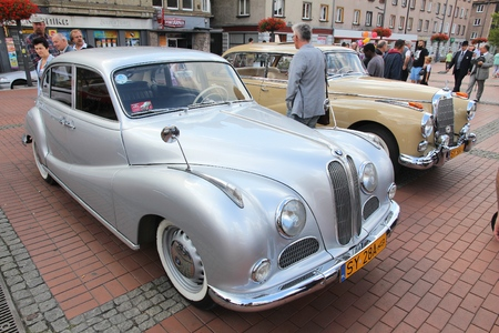 BYTOM, POLAND - SEPTEMBER 12, 2015: People walk by BMW 501 and Mercedes-Benz 300 oldtimer cars during 12th Historic Vehicle Rally in Bytom.
