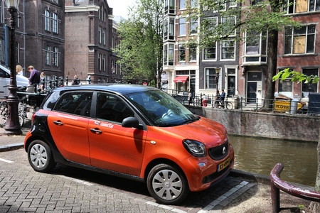 AMSTERDAM, NETHERLANDS - JULY 10, 2017: ConnectCar car sharing vehicle Smart parked by the canal in Amsterdam. Netherlands has 528 registered cars per 1,000 inhabitants. Editorial
