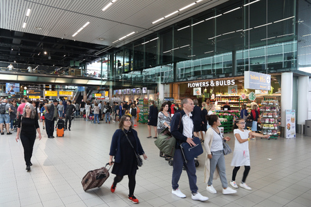 AMSTERDAM, NETHERLANDS - JULY 11, 2017: Travelers visit Schiphol Airport in Amsterdam. Schiphol is the 12th busiest airport in the world with more than 63 million annual passengers.