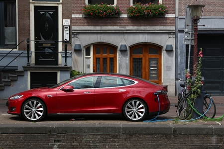 AMSTERDAM, NETHERLANDS - JULY 10, 2017: Electric Tesla Model S car parked by the canal in Amsterdam. Netherlands has 528 registered cars per 1,000 inhabitants.