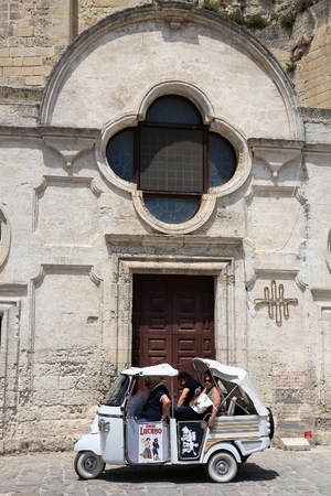 MATERA, ITALY - JUNE 4, 2017: People visit Sassi districts by a Piaggio trike tour in Matera, Italy.