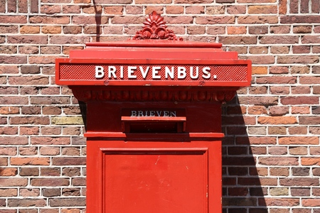 Red post box in Amsterdam, Netherlands. Brievenbus means letter box in Dutch.