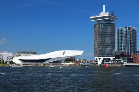 AMSTERDAM, NETHERLANDS - JULY 9, 2017: EYE Film Institute Netherlands (left) in Amsterdam. The structure located in Overhoeks district was designed by Roman Delugan.