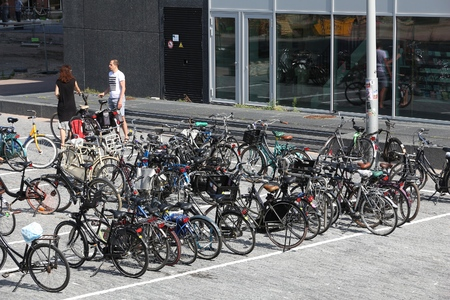 AMSTERDAM, NETHERLANDS - JULY 9, 2017: People visit bicycle parking in Amsterdam. Netherlands is extremely friendly towards bicycles. 報道画像
