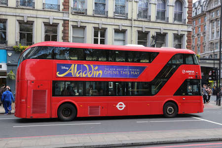 LONDON, UK - APRIL 23, 2016: People ride New Routemaster bus in City of London. The hybrid diesel-electric bus is a new, modern version of iconic double decker.