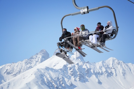 VALLOIRE, FRANCE - MARCH 23, 2015: Skiers go up the lift in Galibier-Thabor station in France. The station is located in Valmeinier and Valloire and has 150km of ski runs.