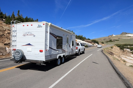 ROCKY MOUNTAINS, USA - JUNE 19, 2013: People drive with camping trailer along Trail Ridge Road in Rocky Mountain National Park, Colorado. RNMP has 3,176,941 annual visitors (2011). Stock Photo - 93587978