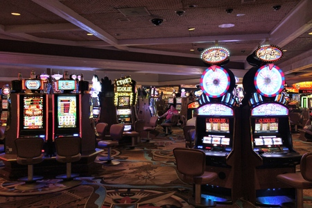 LAS VEGAS, USA - APRIL 14, 2014: People visit slot machinesTreasure Island casino resort in Las Vegas. It is one of 30 largest hotels in the world with 2,884 rooms.