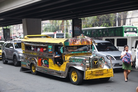 MANILA, PHILIPPINES - NOVEMBER 25, 2017: People ride a jeepney public transportation in heavy traffic in Manila, Philippines. Metro Manila is one of the biggest urban areas in the world with 24 million people.