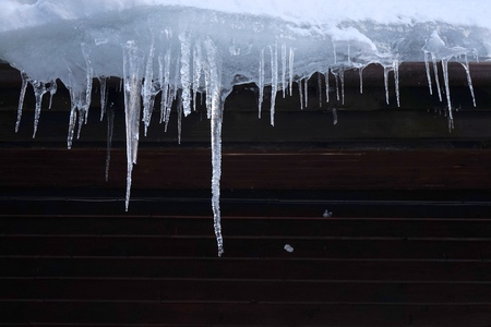 Wooden cabin roof icicles in winter. Icicles signify insufficient building insulation and thermal losses.