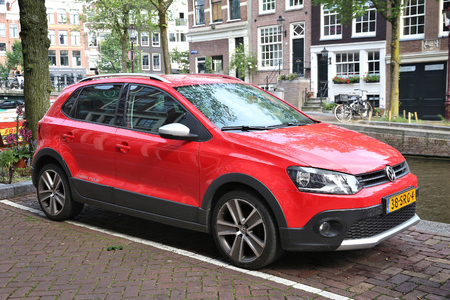 AMSTERDAM, NETHERLANDS - JULY 8, 2017: Red Volkswagen Polo Cross small city car parked by the canal in Amsterdam. Netherlands has 528 registered cars per 1,000 inhabitants. 新聞圖片