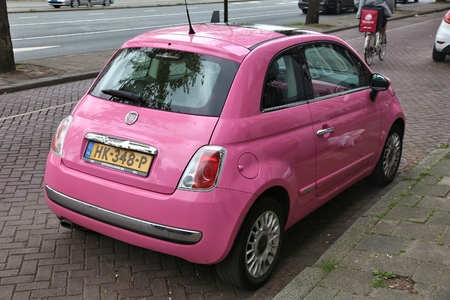 AMSTERDAM, NETHERLANDS - JULY 8, 2017: Pink Fiat 500 small city car parked by the canal in Amsterdam. Netherlands has 528 registered cars per 1,000 inhabitants.