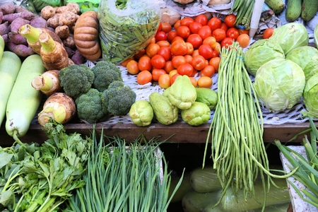 Fresh vegetables market in Chinatown, Manila, Philippines with taro roots, broccoli, ampalaya (bitter melon), long beans, tomatoes, cabbage and chives. Stock Photo