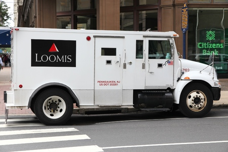 PHILADELPHIA, USA - JUNE 11, 2013: Loomis armored money truck in Philadelphia, USA. Loomis is a cash handling company operating 3,000 money vehicles in the US.