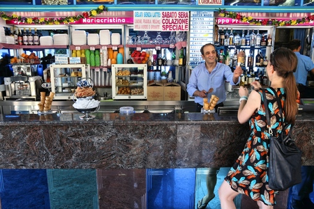 POLIGNANO A MARE, ITALY - MAY 29, 2017: Ice cream vendor makes gelato in traditional gelateria in Polignano a Mare, Italy. With 50.7 million annual visitors Italy is one of the most visited countries.