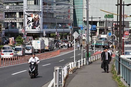 TOKYO, JAPAN - MAY 11, 2012: People visit Shinjuku district, Tokyo. Shinjuku is one of the busiest districts of Tokyo, with many international corporate headquarters located here.