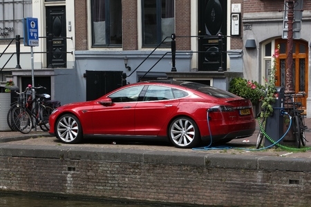 AMSTERDAM, NETHERLANDS - JULY 10, 2017: Electric Tesla Model S car charged by the canal in Amsterdam. Netherlands has 528 registered cars per 1,000 inhabitants.