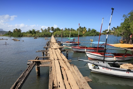 BARACOA, CUBA - FEBRUARY 12, 2011: Boats by Rio Miel footbridge in Baracoa. The area is part of Alejandro de Humboldt National Park. 免版税图像 - 115573959