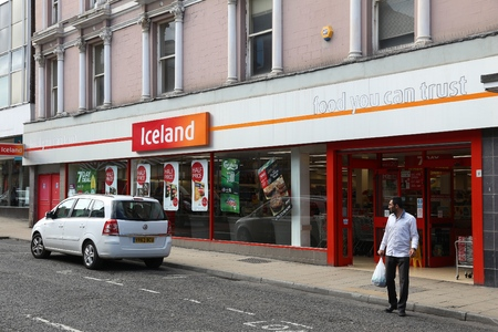 BARNSLEY, UK - JULY 10, 2016: Man exits Iceland store in Barnsley, UK. The frozen foods company Iceland has 814 stores in the UK. Banque d'images - 115573983