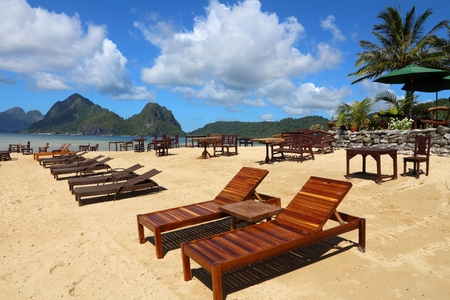 Paradise beach landscape - Las Cabanas beach in El Nido, Palawan island, Philippines. Wooden sunbeds. Stock Photo