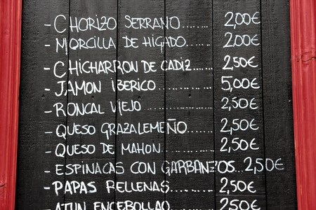 SEVILLE, SPAIN - NOVEMBER 3, 2012: Spanish restaurant blackboard menu in Seville, Spain. Seville is a major tourism destination in Spain with 4.8 million hotel-nights in 2011. Editorial