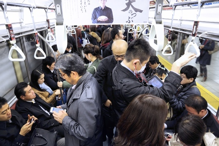 TOKYO, JAPAN - 2. DEZEMBER 2016: Passagiere fahren mit einem überfüllten U-Bahn-Zug in Tokio. Mit mehr als 3,1 Milliarden Fahrgästen pro Jahr ist das U-Bahn-System von Tokio das verkehrsreichste weltweit.