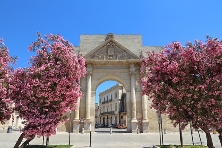 Lecce, Italy - city in Salento peninsula. Porta Napoli Triumphal Arch with oleander flowers.