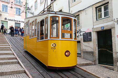 LISBON, PORTUGAL - JUNE 6, 2018: People ride the Bica Funicular (Ascensor de Bica) railway line in Lisbon, Portugal. Lisbon in renowned for its historical funicular trams and yellow streetcars. Editorial