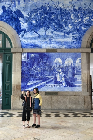 PORTO, PORTUGAL - MAY 24, 2018: Tourists take a selfie at Sao Bento Station in Porto, Portugal. The railway station dates back to 1864 and is one of main train stations in Portugal.
