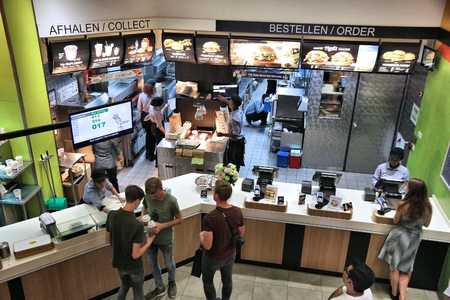 AMSTERDAM, NETHERLANDS - JULY 10, 2017: Employees work the kitchen of McDonald's restaurant in Amsterdam. McDonald's is the world's largest restaurant chain with 69 million customers served daily.