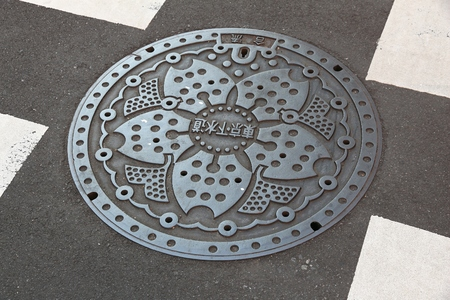 TOKYO, JAPAN - NOVEMBER 30, 2016: Ornamented manhole cover in Tokyo. Japan frequently has beautiful decorative sewer covers.