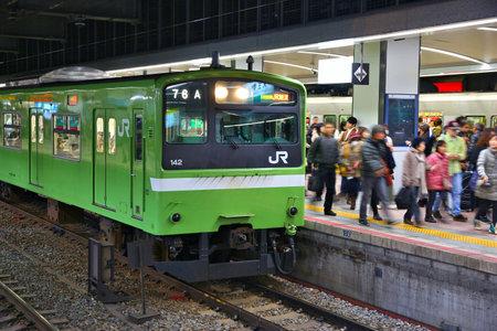 OSAKA, JAPAN - NOVEMBER 23, 2016: Passengers board JR train at Tennoji Station in Osaka, Japan. JR West Tennoji Station served 143,202 passengers daily in 2015. Редакционное