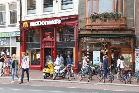 AMSTERDAM, NETHERLANDS - JULY 8, 2017: People walk by McDonald's restaurant in Amsterdam, Netherlands. McDonald's is the world's largest restaurant chain with 69 million customers served daily.