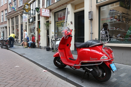 AMSTERDAM, NETHERLANDS - JULY 8, 2017: Red Piaggio Vespa scooter parked in Amsterdam, Netherlands. Vespa regained its popularity in recent years.