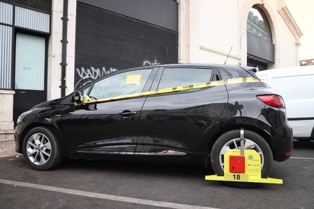 LISBON, PORTUGAL - JUNE 6, 2018: Parking issue in Lisbon, Portugal. Clamped wheel for illegal parking. EMEL is Lisbon's municipal parking authority.